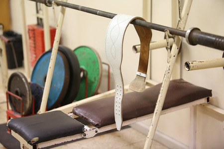 powerlifting: belt and colourful weights for powerlifting on a rack Stock Photo