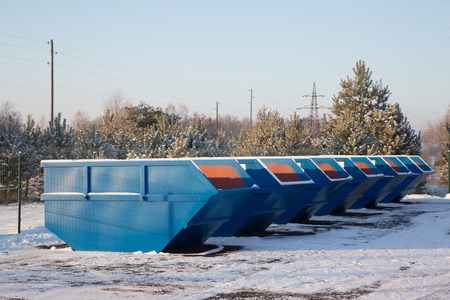 discarded: Row of blue large garbage containers at winter day on the open place