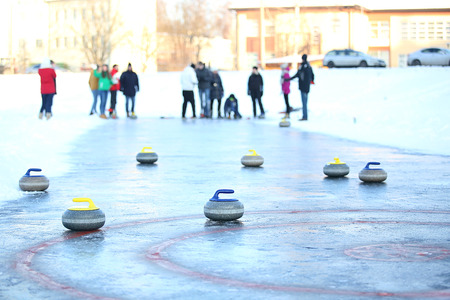 People playing in curling on the surface of frozen lake