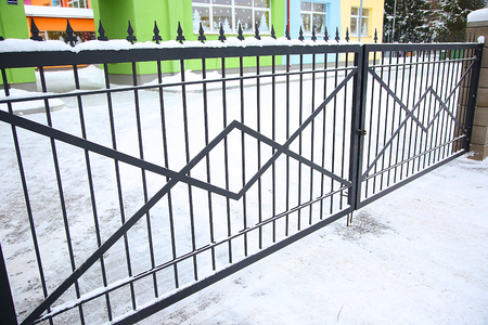 closed community: Forged gates at winter time covered by snow