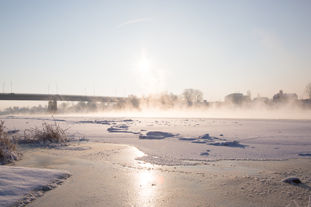 snowscape: Winter. Frozen river with steam above surface and bridge background. Sunnny time. Daylight
