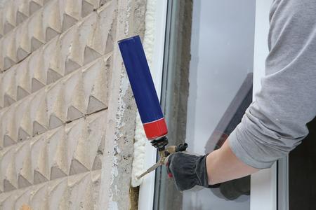 Worker's hand fix a window using polyurethane foam Stock Photo