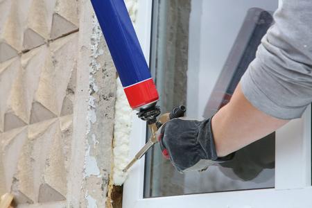 Mano dell'operaio fissare una finestra utilizzando schiuma poliuretanica