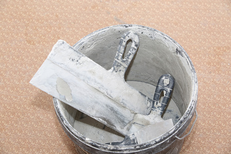putty knives: Putty knifes in bucket. Flat is under construction Stock Photo