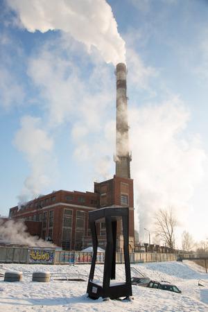 dedication: DAUGAVPILS, LATVIA - JANUARY 6, 2016: heating plant with big smoking chimney and abstract monument dedication Rothko