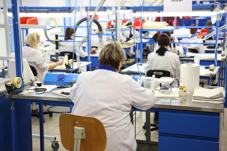 bata blanca: Vista trasera de los trabajadores en la capa blanca en el lugar de trabajo