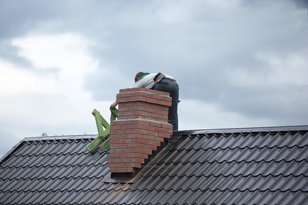 Worker on the roof repairs brick chimney 스톡 콘텐츠