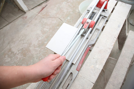 tile cutter: Worker holds the handle of ceramic tile cutter with tile