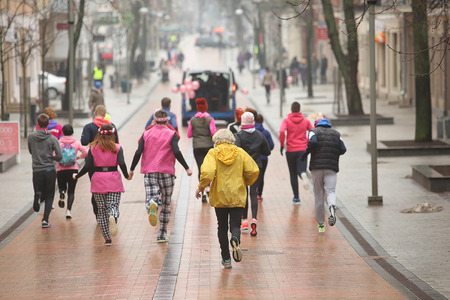 sidewalk talk: Rear view of Group of running people on the city street Editorial