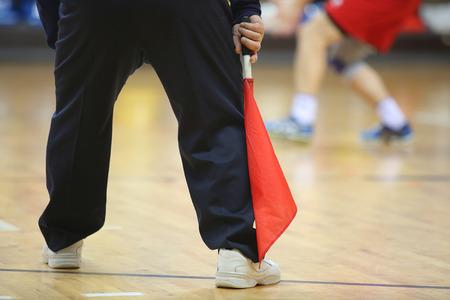 árbitro de voleibol en la línea con el indicador rojo