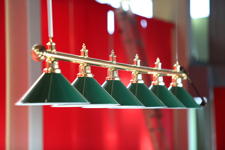 billiards rooms: Row of Billiard green  lamps above table