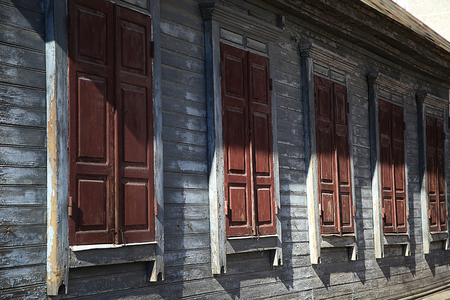 cracky: row of windows with closed shutters of wooden house Stock Photo