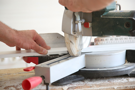 filings: carpenter working with electro circular saw indoor Stock Photo
