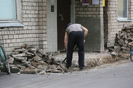 Man working on construction with shovel clean up from broken bricks