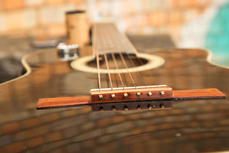 acoustic guitar close-up with strings and lacquered deck