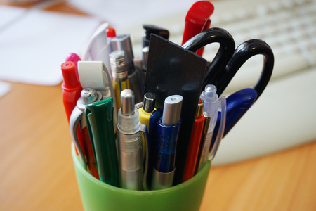 Pens in the glass on table and other stationery