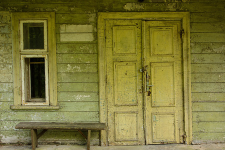 window bench: Wooden door on old wall at abandoned facade near wooden bench and window