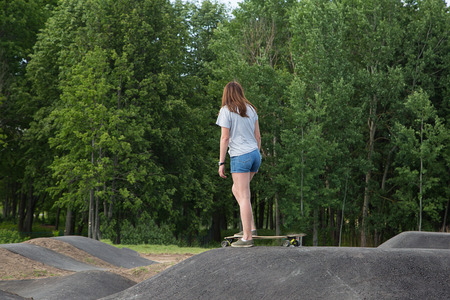 subculture: Girl wearing jeans shorts practicing long board riding in skateboarding park. Active urban life. Urban subculture Stock Photo