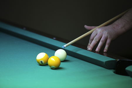 Billiard player . hand with cue prepare hit a ball