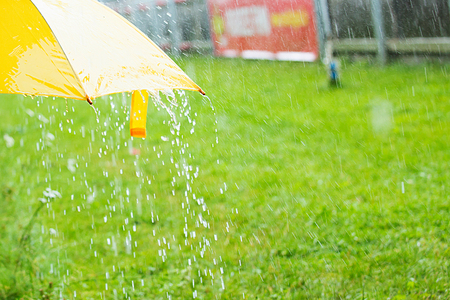 Rain drops falling from a yellow umbrella concept for bad weather Фото со стока - 83382477