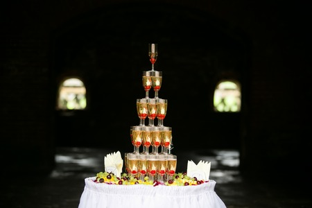Glasses of champagne pyramid made up with fruits