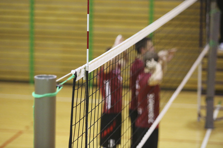 Volleyball net in the sport hall with players on background Reklamní fotografie