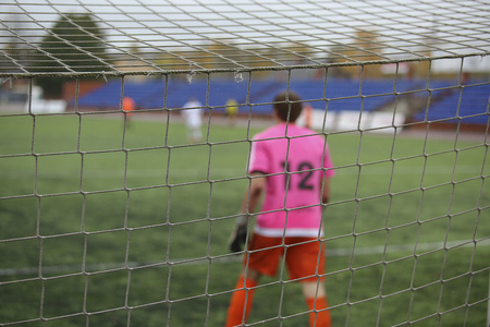 rear view of soccer goalkeeper with net foreground
