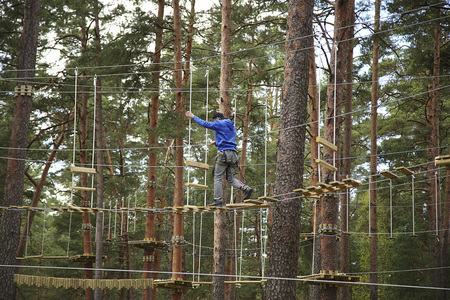 Man climbing in adventure rope park in safety equipment between trees