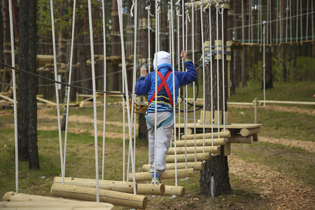 Boy climbing rope at the adventure park