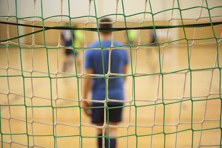 Rear view of futsal goalkeeper with net of gates foreground
