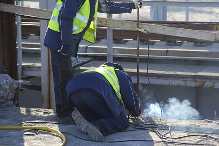 Industrial construction worker using a professional angle grinder for cutting asphalt