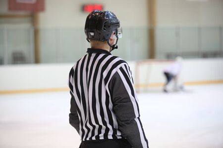 Hockey referee on the ice watching the game