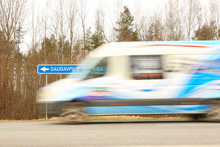 LIVANI DISTRICT, LATVIA - MARCH 19, 2020. car blurred on a highway and road sign Daugavpils - Riga