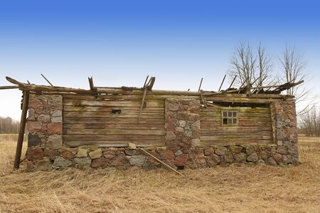 Old stone barn almost fallen with wooden roof top cover and holes