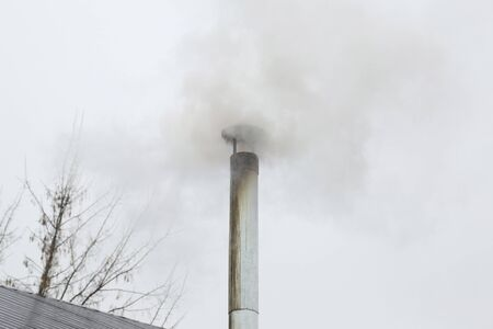 Metal chimney on the roof with smoke
