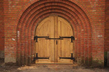 Old wooden door in red brick church. Front view