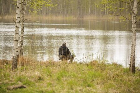 Fisherman sits on the seat on the coast of lake with fishing rod Standard-Bild