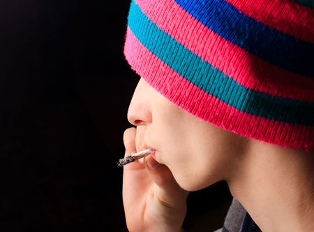 Boy in multicolored hat smokes Stock Photo