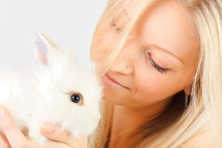Young girl holding a white little rabbit photo
