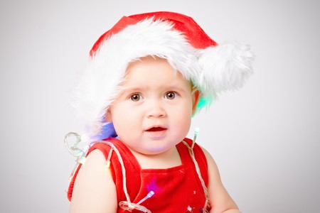 Baby in Santa Claus hat on white background photo
