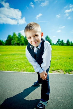 Little boy in a shirt and vest in park photo