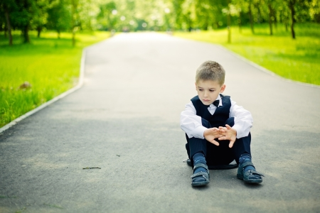 boy sitting down in a park photo