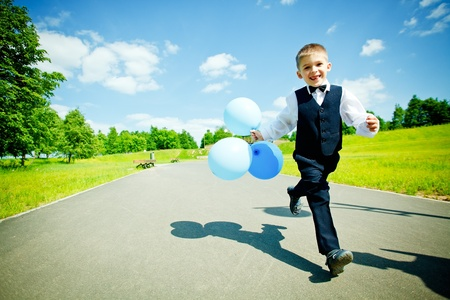 Young boy moving with balloons photo