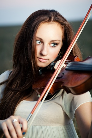 Young girl playing violin over nature Stock Photo - 10435652