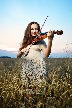 Young girl playing violin over nature
