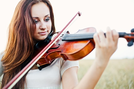 woman violin: Young girl playing violin over nature