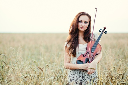 Young girl with violin over nature photo