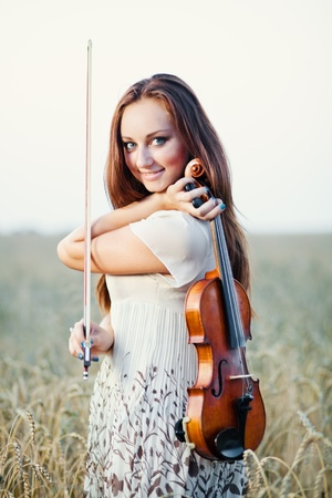 Young girl with violin over nature