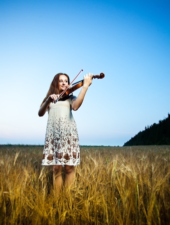 Young girl playing violin over nature photo