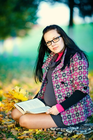 Pregnant woman in autumn park reading book photo